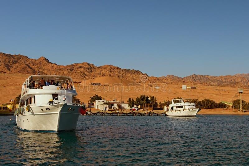Kryssningskeppet med turister går till reven var folket ska dyka med dykning eller att snorkla för dykapparat royaltyfri fotografi