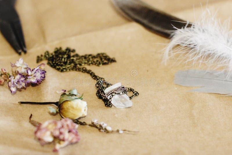 Krystaliczna kolia, piórko i suszący kwiaty na rzemiosła tle, zdjęcie royalty free