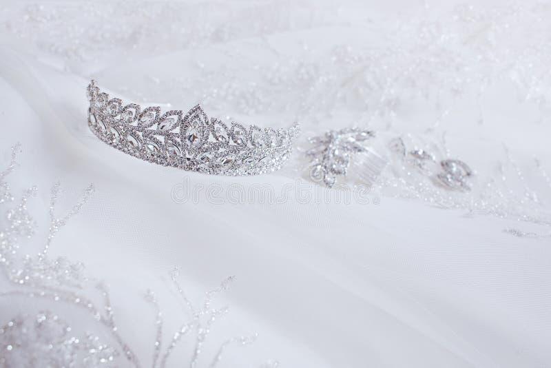 Krystaliczny jewellery: kolczyki, hairpin, diadem na białym ślubnym tle obrazy stock