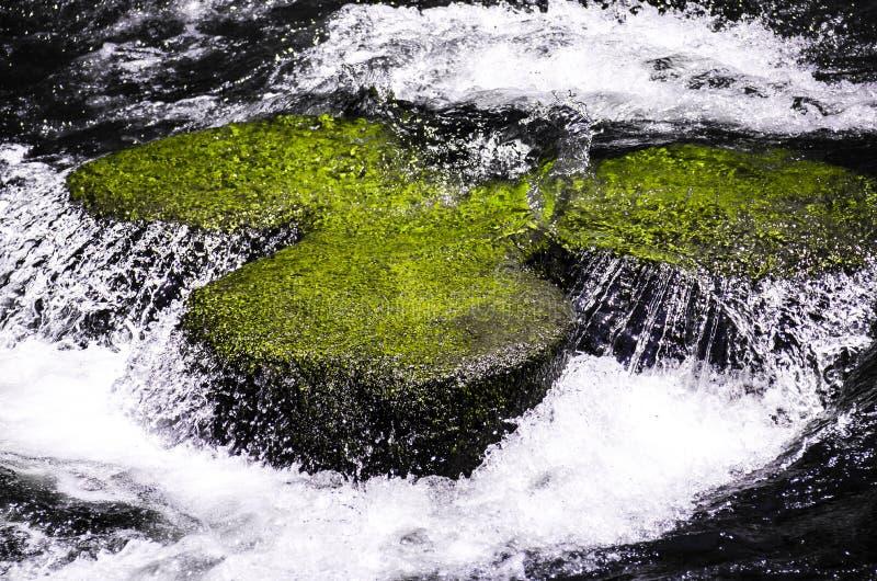 Kryształ nawadnia nad Zieloną skałą fotografia stock
