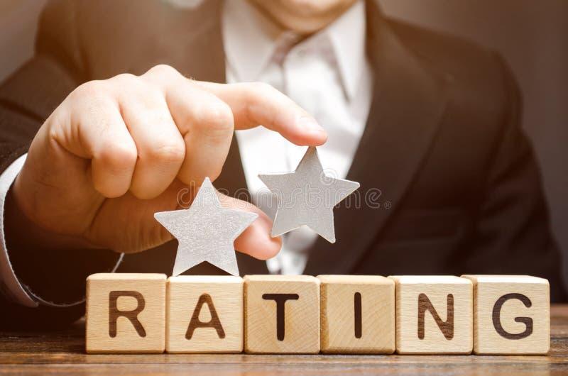 Krytyk stawia drugi gwiazdę nad słowo ocena na drewnianych blokach Pojęcie ilość usługa Hotelowa lub restauracyjna ocena fotografia stock