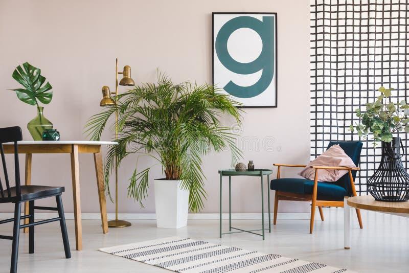 Krzesło przy stołem z liściem w mieszkania wnętrzu z roślinami, drewnianym karłem i plakatem, Istna fotografia zdjęcie royalty free