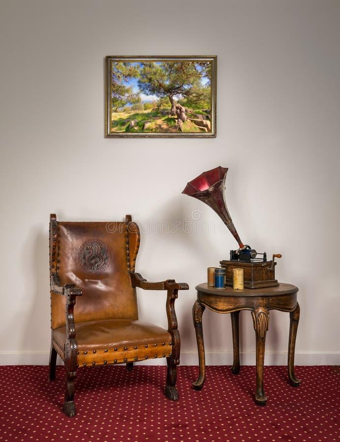 Krzesło retro ornate, stary fonograf, cylindry na stoliku kawowym zdjęcia stock