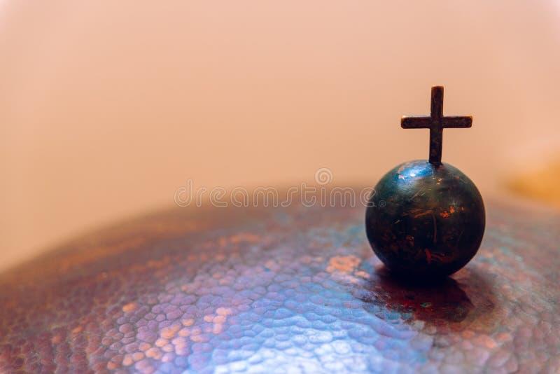 Krzyż chrześcijański na małej metalowej kuli, przestrzeń negatywna obrazy royalty free