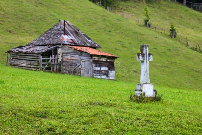 Krzyż i dom w Rumunia góry wsi zdjęcia stock