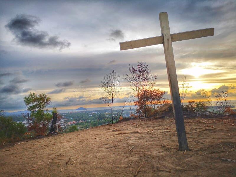 Krzyż na wierzchołku wzgórze przed zmierzchu spadkiem fotografia royalty free
