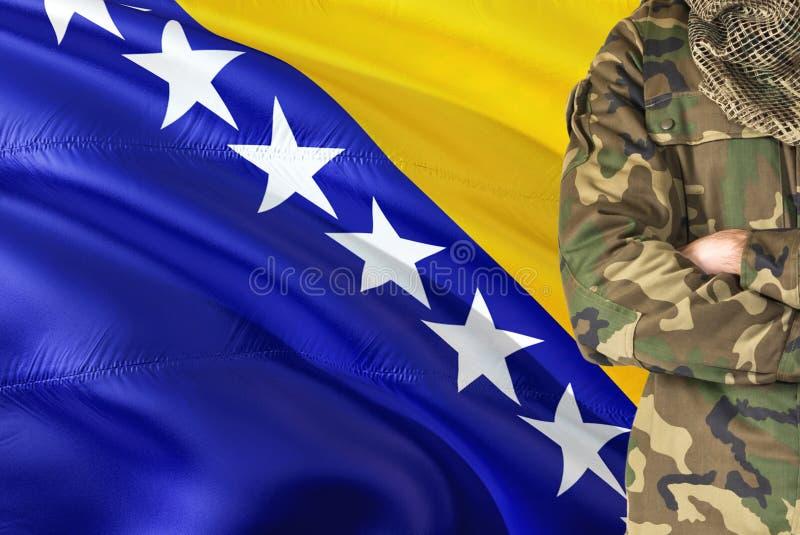 Krzyżujący ręka Bośniacki żołnierz z krajową falowanie flagą na tle Bośnia, Herzegovina wojskowego temat - zdjęcie royalty free