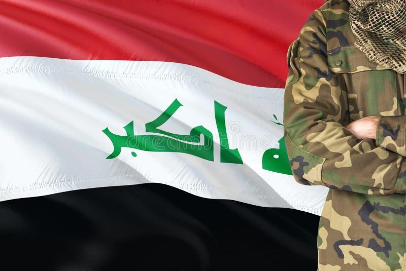 Krzyżujący ręka Irakijski żołnierz z krajową falowanie flagą na tle - Iracki Militarny temat obraz royalty free