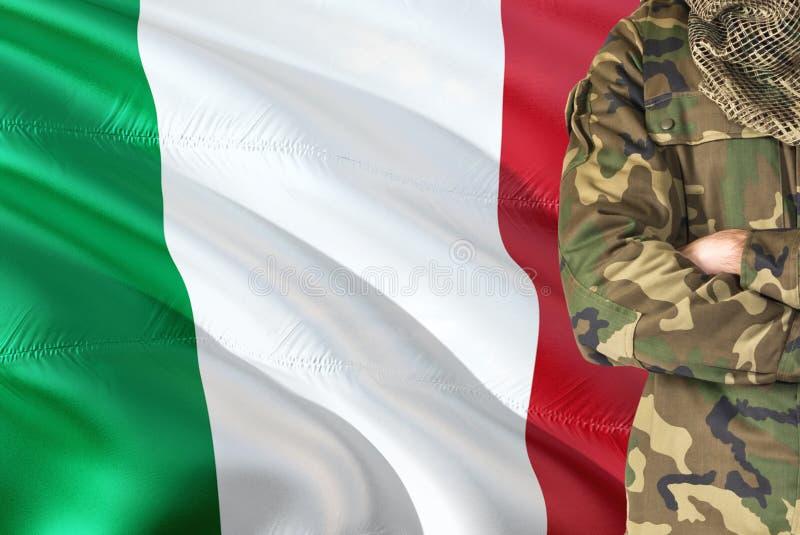 Krzyżujący ręka Włoski żołnierz z krajową falowanie flagą na tle - Włochy wojskowego temat obraz stock
