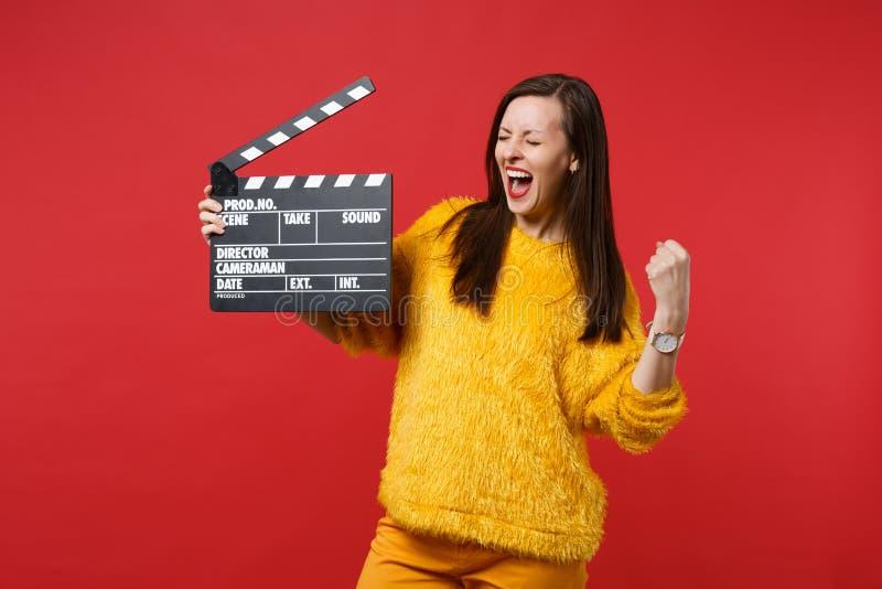 Krzycząca młoda kobieta z zamkniętymi oczami robi zwycięzcy gestykuluje, trzymający klasycznego czarnego ekranowego robić clapper obrazy royalty free