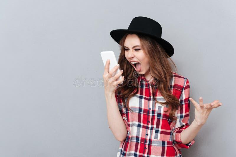 Krzycząca gniewna młoda kobieta opowiada telefonem komórkowym fotografia stock