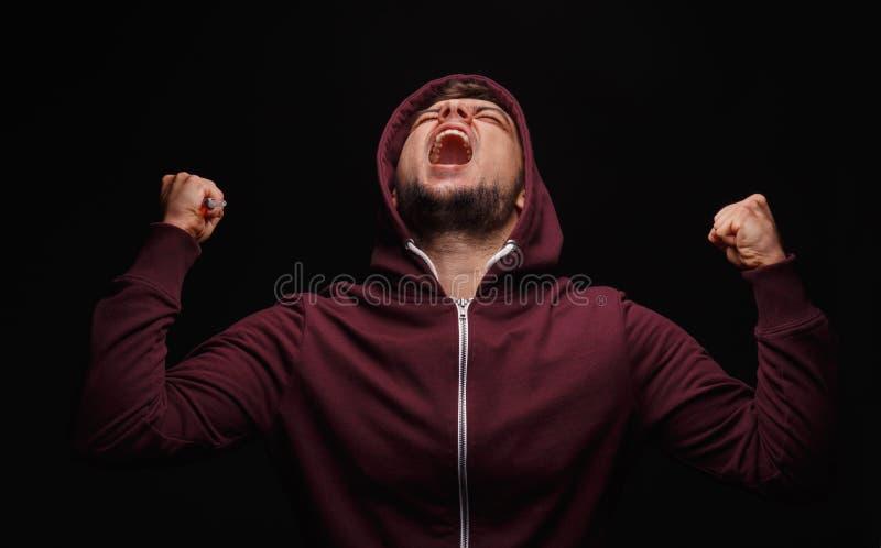 Krzyczący, chora samiec na czarnym tle Zaakcentowany uczeń w hoodie Mężczyzna cierpienie w bólu Złość wydaje pojęcie zdjęcia royalty free