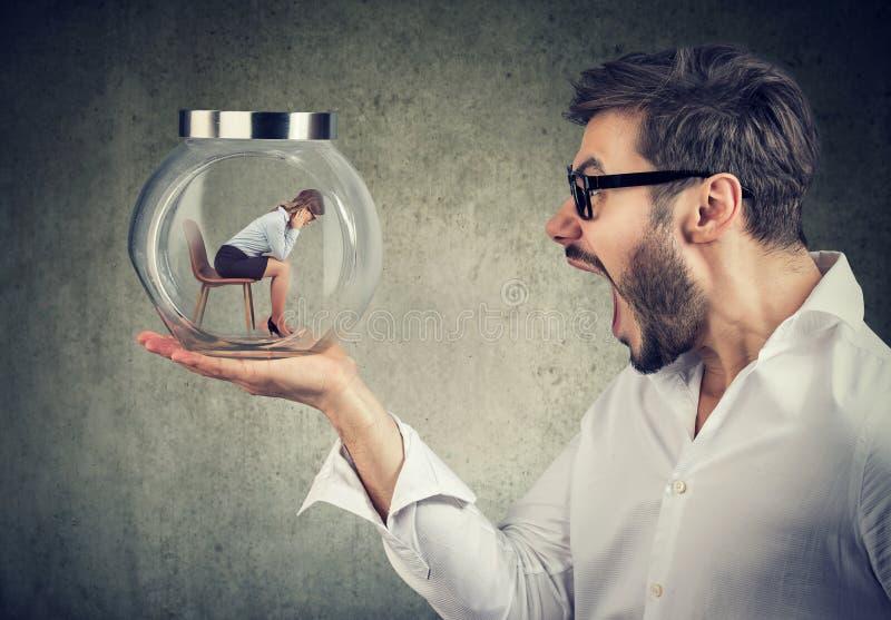 Krzyczący mężczyzna trzyma szklanego słój z kobietą wśrodku fotografia stock