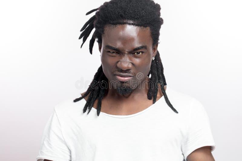 Krzyczący młody afrykański mężczyzna stoi białego tło z dreadlocks przyglądająca kamera zdjęcie royalty free