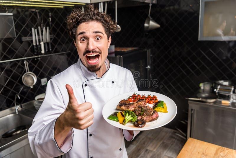 krzyczący uśmiechnięty szef kuchni pokazuje kciuk w górę i trzyma gotujących warzywa obraz royalty free