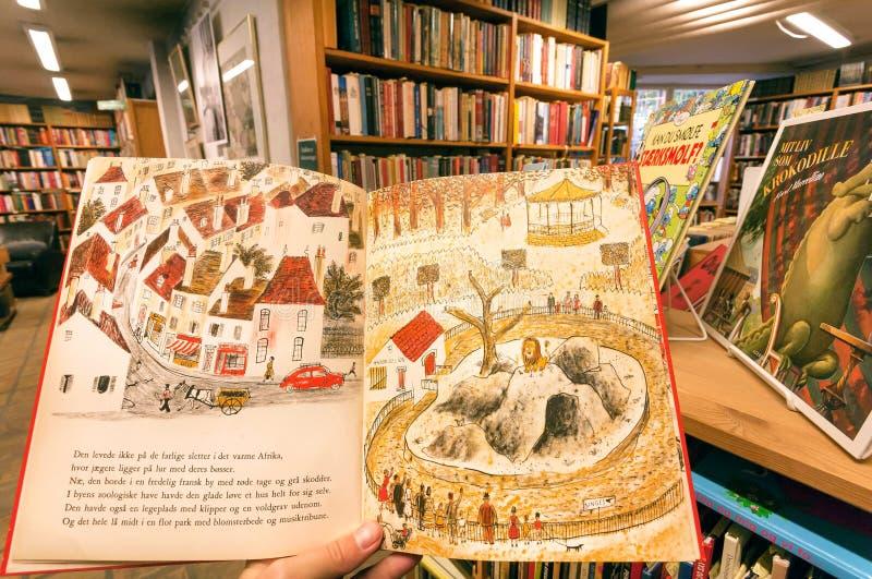 Książki dla dzieci w rękach klient, wśrodku dzieciaka wyboru bookstore zdjęcia stock