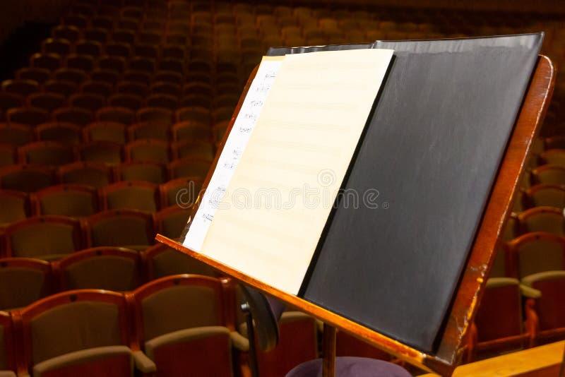 Książka muzyczna i kartki z notacją muzyczną na stoisku gotowym na koncert Wyposażenie Orkiestry w Filharmonii fotografia stock