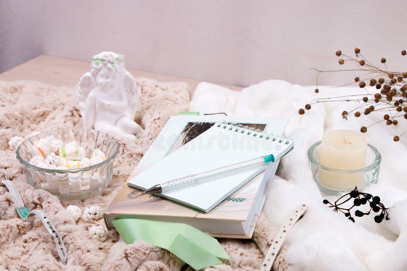 Książka, notatnik, świeczka w szklanym candlestick, parvarda, arachidy w cukierze, posążek anioł robić biały tynk fotografia royalty free