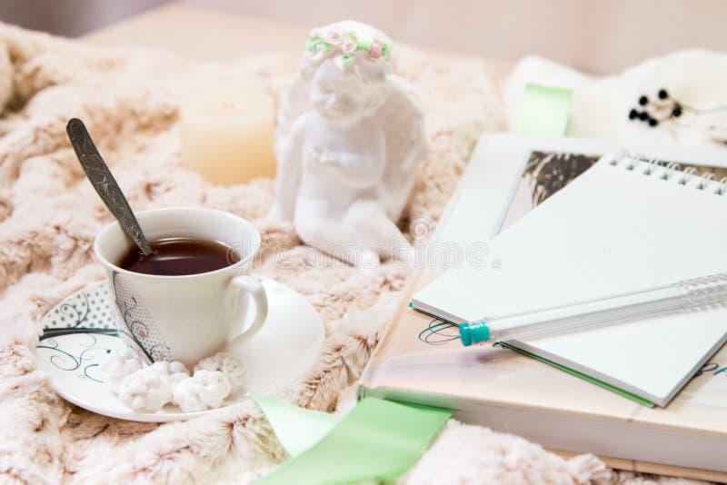 Książka, notatnik, świeczka w szklanym candlestick, parvarda, arachidy w cukierze, posążek anioł robić biały tynk, a obrazy stock
