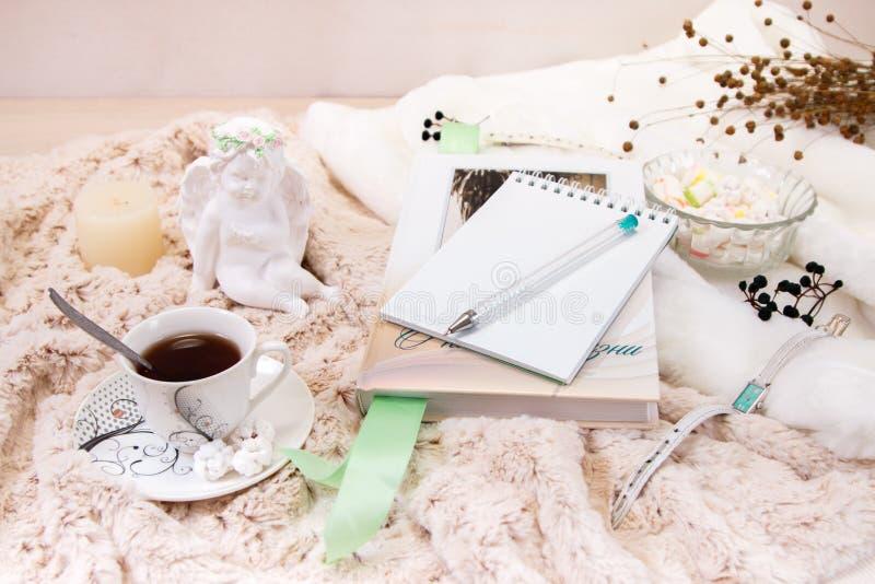 Książka, notatnik, świeczka w szklanym candlestick, parvarda, arachidy w cukierze, posążek anioł robić biały tynk, a zdjęcie stock
