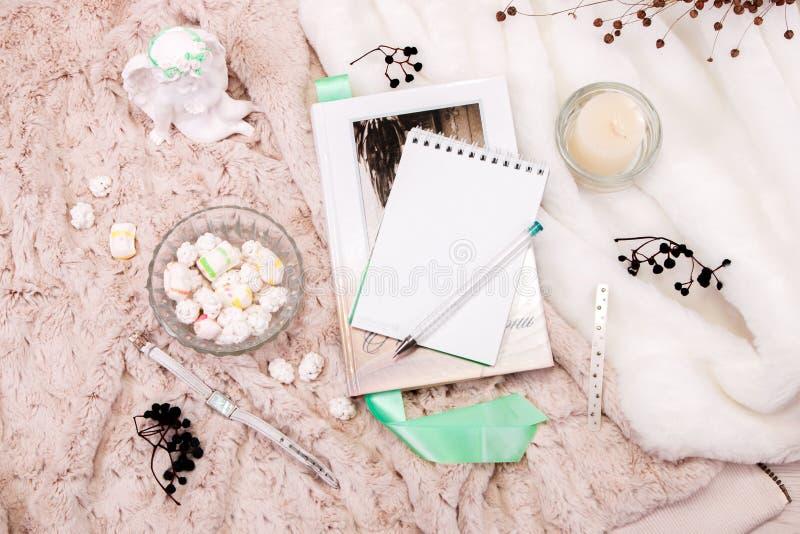 Książka, notatnik, świeczka w szklanym candlestick, parvarda, arachidy w cukierze, posążek anioł robić biały tynk, a obraz royalty free