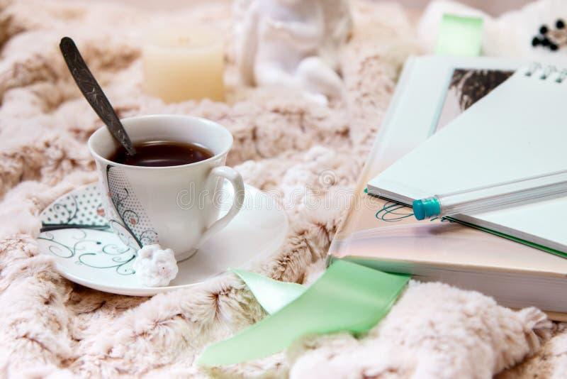 Książka, notatnik, filiżanka czarna kawa, arachidy w cukierze, świeczka, statua anioł od tynku na miękkiej części, beżowa koc obrazy stock