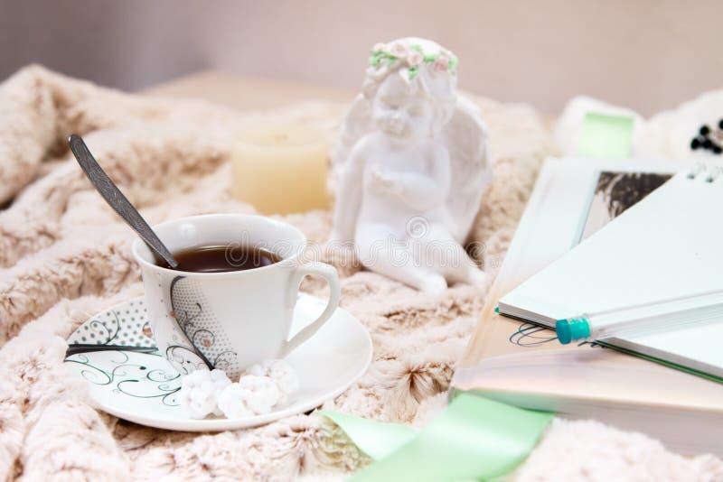 Książka, notatnik, filiżanka czarna kawa, arachidy w cukierze, świeczka, statua anioł od tynku na miękkiej części, beżowa koc zdjęcie stock