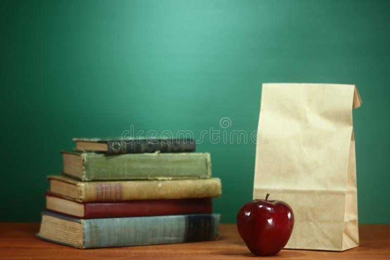 Książki, Apple i lunch na nauczyciela biurku, fotografia stock