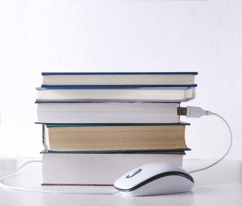 Książki i komputerowa mysz przeciw biel ścianie poj?cie uczenie e zdjęcie stock