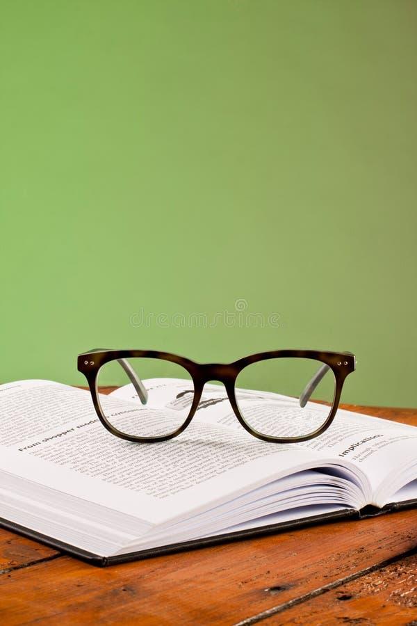 Książki i szkła na drewnianym stole zdjęcia stock