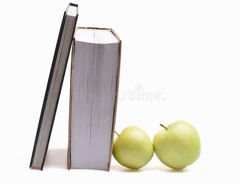 Książki i zieleni jabłka odizolowywający na bielu obrazy stock