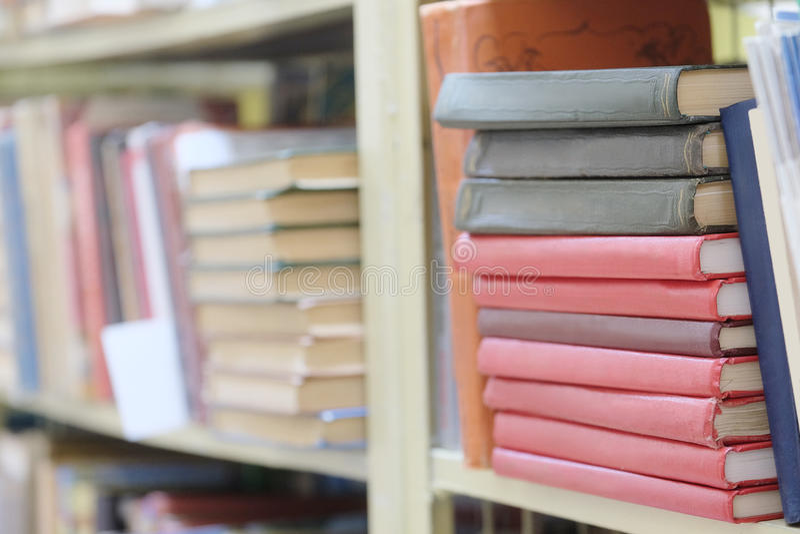 Książki na półce w bibliotece obrazy stock