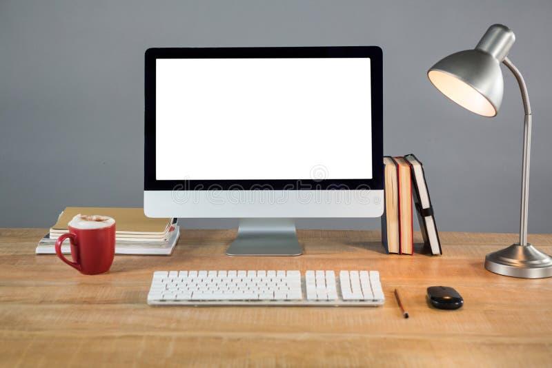 Książki, stołowa lampa i komputer stacjonarny na stole, obrazy royalty free