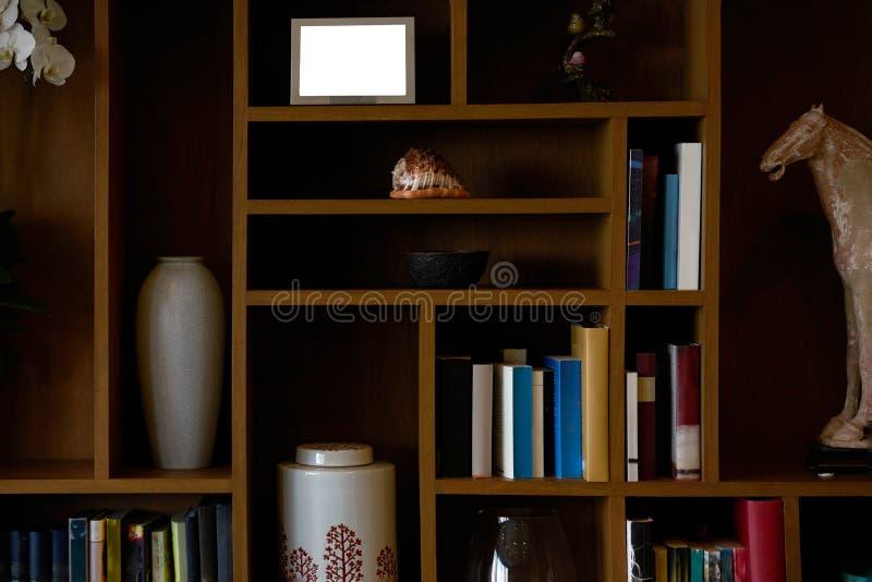 Książkowa półka z faszeruje dekorację tak jak książki, słój, skalpu koń, obrazek rama obrazy royalty free