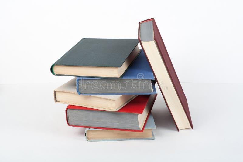 Książkowa sterta, hardback kolorowe książki na drewnianym stole, biały tło tylna szkoły Odbitkowa przestrzeń dla teksta Edukacja zdjęcia royalty free