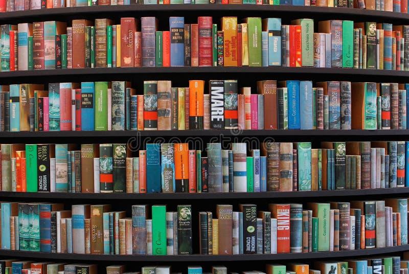 Książkowe półki w bibliotecznych różnych językach obraz royalty free