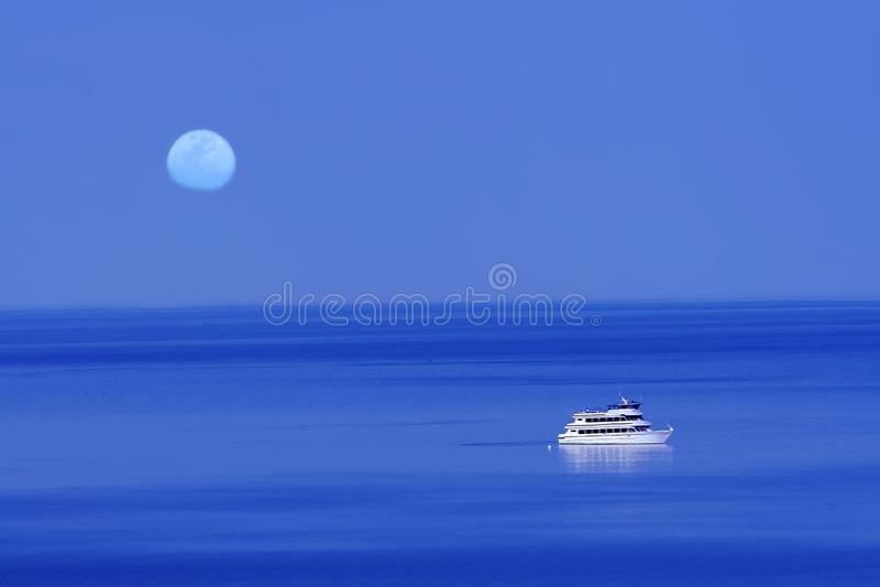 Księżyc nad błękitnym jeziorem z łodzią obraz royalty free