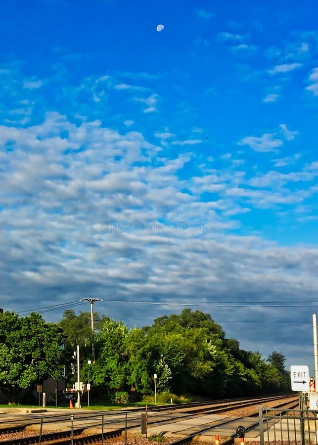 Księżyc położenie nad stratocumulusu cloudscape widzieć od ulicznego skrzyżowania który zakrywa pociąg poruszającego na torze szy zdjęcie royalty free