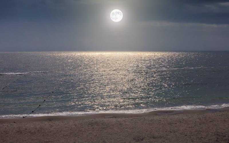 Księżyc w nocnym niebie nad blask księżyca wodą morską obraz stock