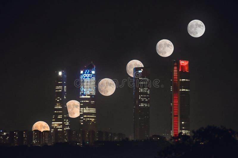 Księżyc w pełni sekwencja nad Cuatro Torres biznesowego terenu linią horyzontu przy nocą w Madryt, Hiszpania obrazy royalty free