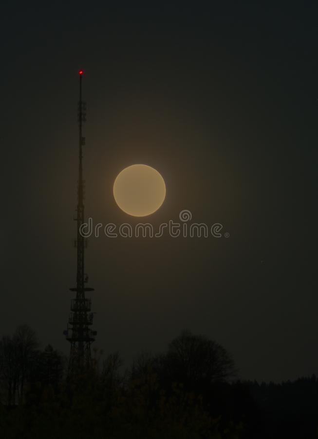 Księżyc w pełni wydźwignięcie w nocne niebo z radiową anteną i przekaz górujemy z czerwonym sygnałowym światłem zdjęcia royalty free