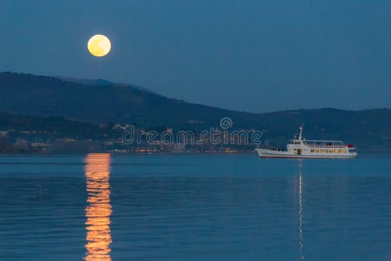 Księżyc w pełni wzrasta nad niektóre wzgórzami na Trasimeno jeziorze, doskonale odbija na wodzie z promem niedalekim obrazy stock