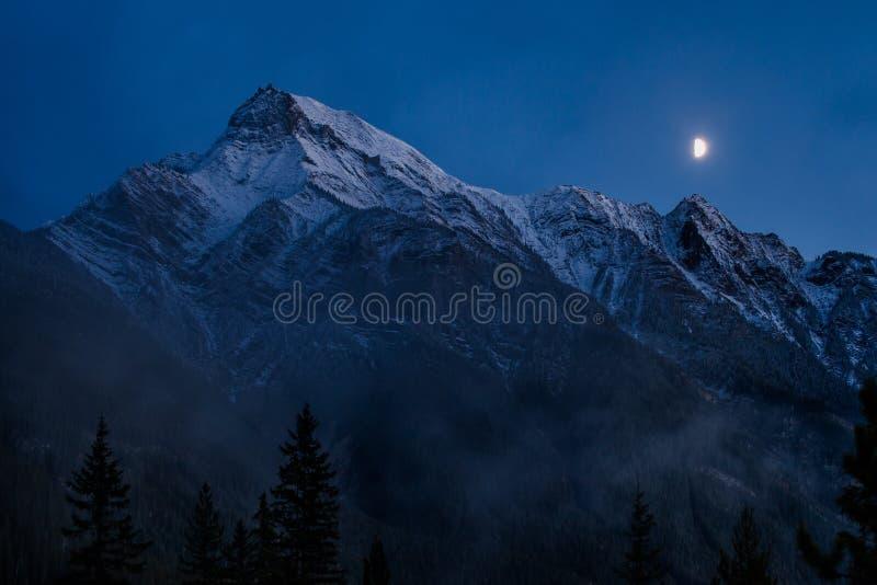 Księżyc wzrasta nad śnieżnym pasmem górskim na mgłowym wieczór obrazy stock