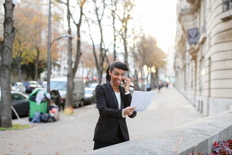 Księgowy pozycja na ulicie z papierami w rękach i opowiadać o zdjęcie stock