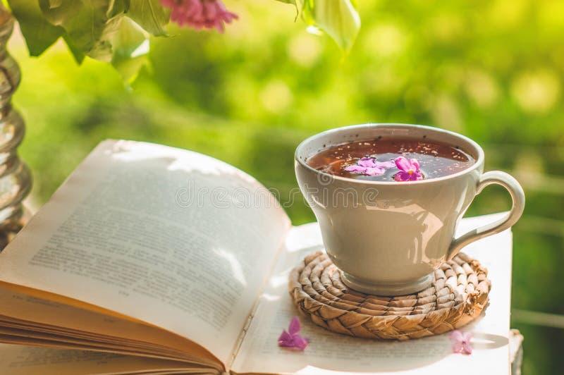 Ksi??ka, szk?a, fili?anka herbata i bez na drewnianym okno, Fragrant herbata w ogr?dzie Romantyczny poj?cie zdjęcie stock