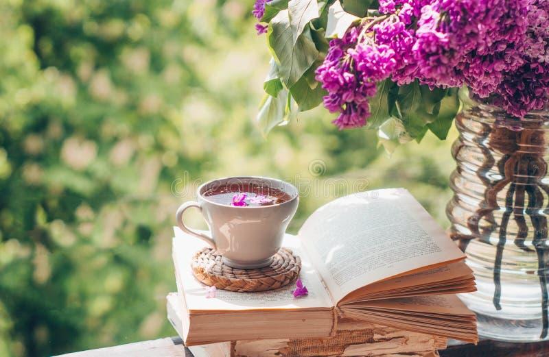 Ksi??ka, szk?a, fili?anka herbata i bez na drewnianym okno, Fragrant herbata w ogr?dzie Romantyczny poj?cie zdjęcia royalty free