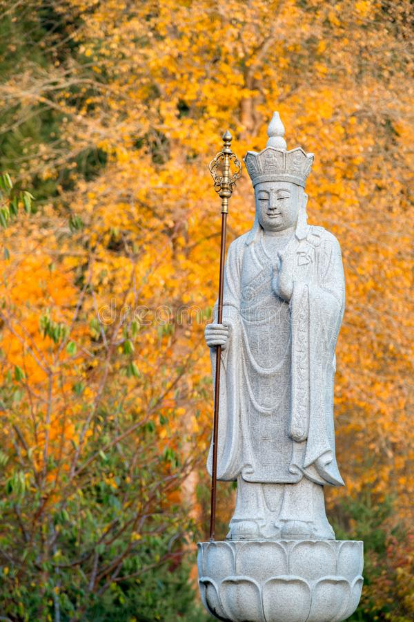 Free Ksitigarbha Buddha, A Bodhisattva, Statue With Yellow Fall Colors In The Background Stock Photos - 163131593