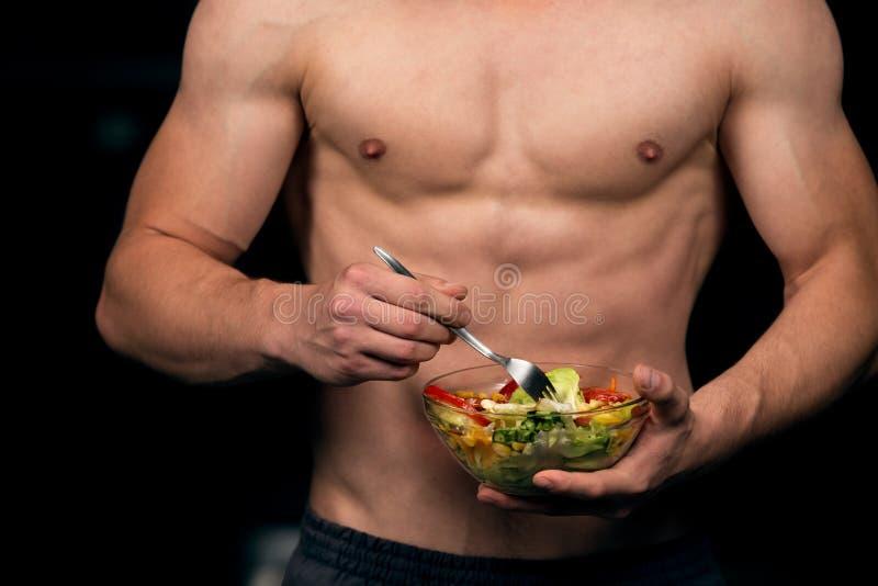 Kształtny i zdrowy ciało budynku mężczyzna trzyma świeżego sałatkowego puchar, kształtny brzuszny zdjęcie stock