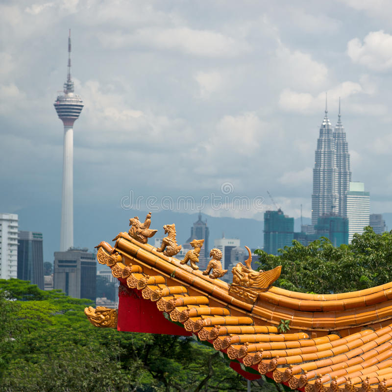 Kuala Lumpur cityscape. Mixture of architectural styles in Kuala Lumpur, Malaysia. The roof of ancient chinese temple on the background of two symbols of Kuala royalty free stock photo