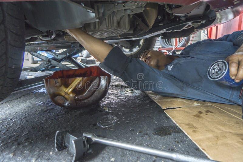 KUALA LUMPUR, 22 DEC 2016 Werktuigkundige die in de workshop van het autoonderhoud werken stock afbeelding